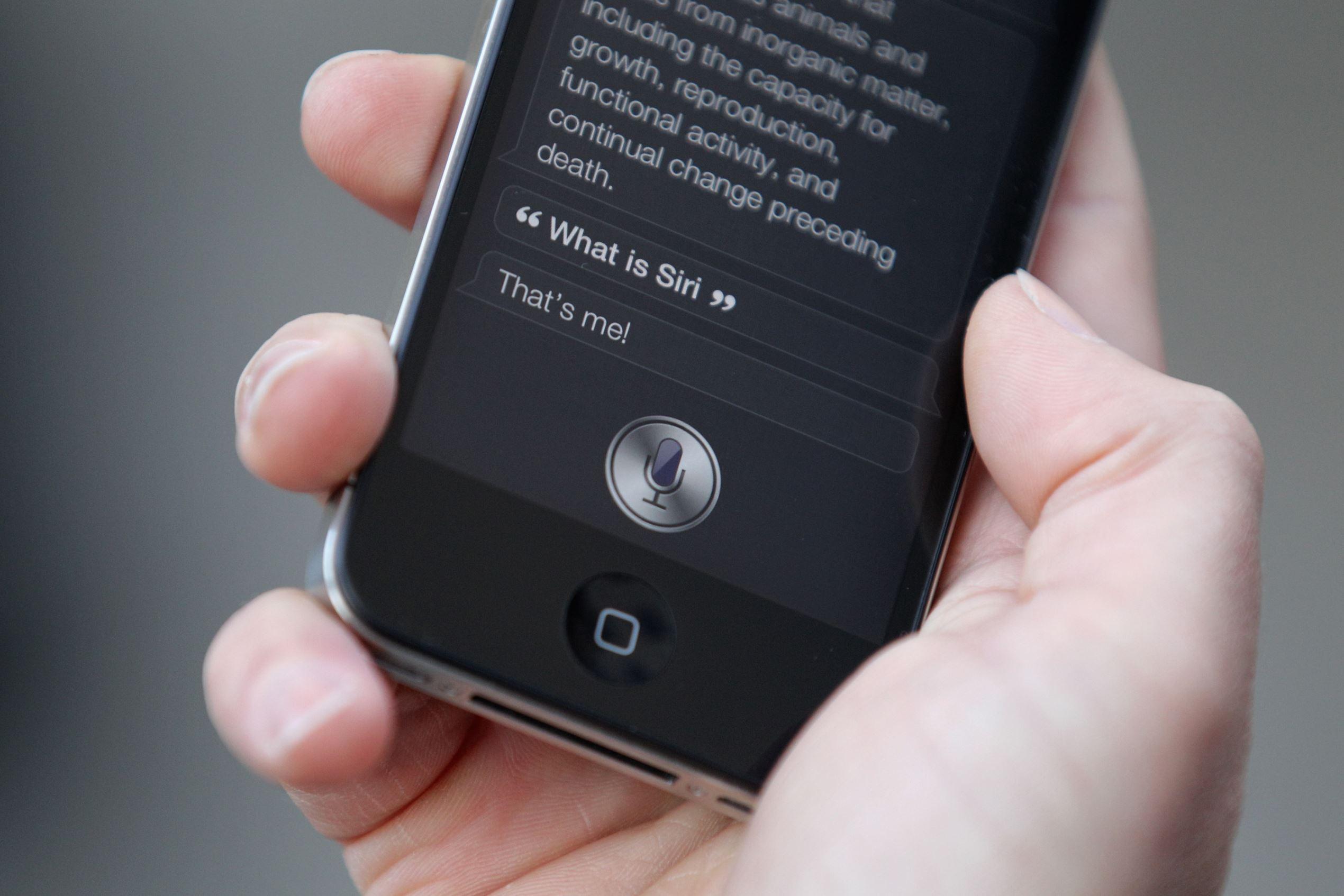 Um homem usa & # 39; Siri & # 39;  sobre o novo iPhone 4S depois de ter sido um dos primeiros clientes na loja da Apple em Covent Garden em 14 de outubro de 2011 em Londres, Inglaterra.