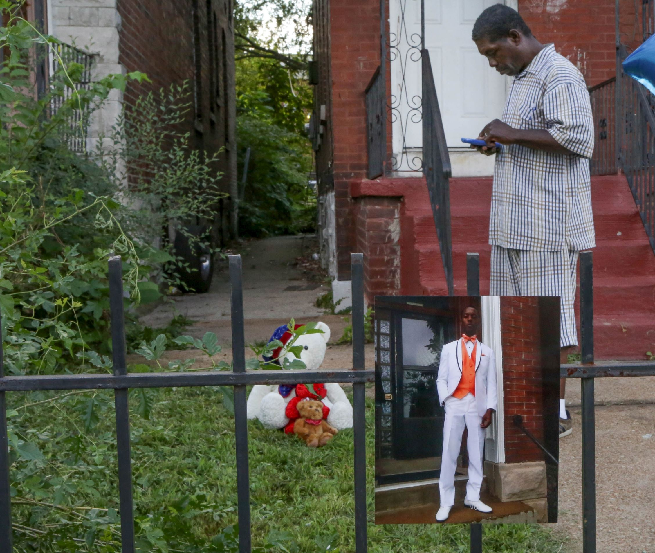 Dennis Ball-Bey, the father of Mansur Ball-Bey, stands in front of the steps where police shot his son as a photo of Mansur hangs on the fence in St. Louis, Missouri, United States, August 20, 2015. The St. Louis police on Wednesday fatally shot Mansur Ball-Bey, a black teenager who they say pointed a gun at them, and later faced angry crowds, reigniting racial tensions first sparked by the killing of an unarmed black teen in another Missouri town a year ago. St. Louis Police Chief Sam Dotson said the shooting took place when young black men ran out of the back door of a house where officers were carrying out a search warrant. Officers ordered the pair to stop in an alley behind the house. One suspect pointed a gun at officers who then fired four times, killing him, Dotson said.