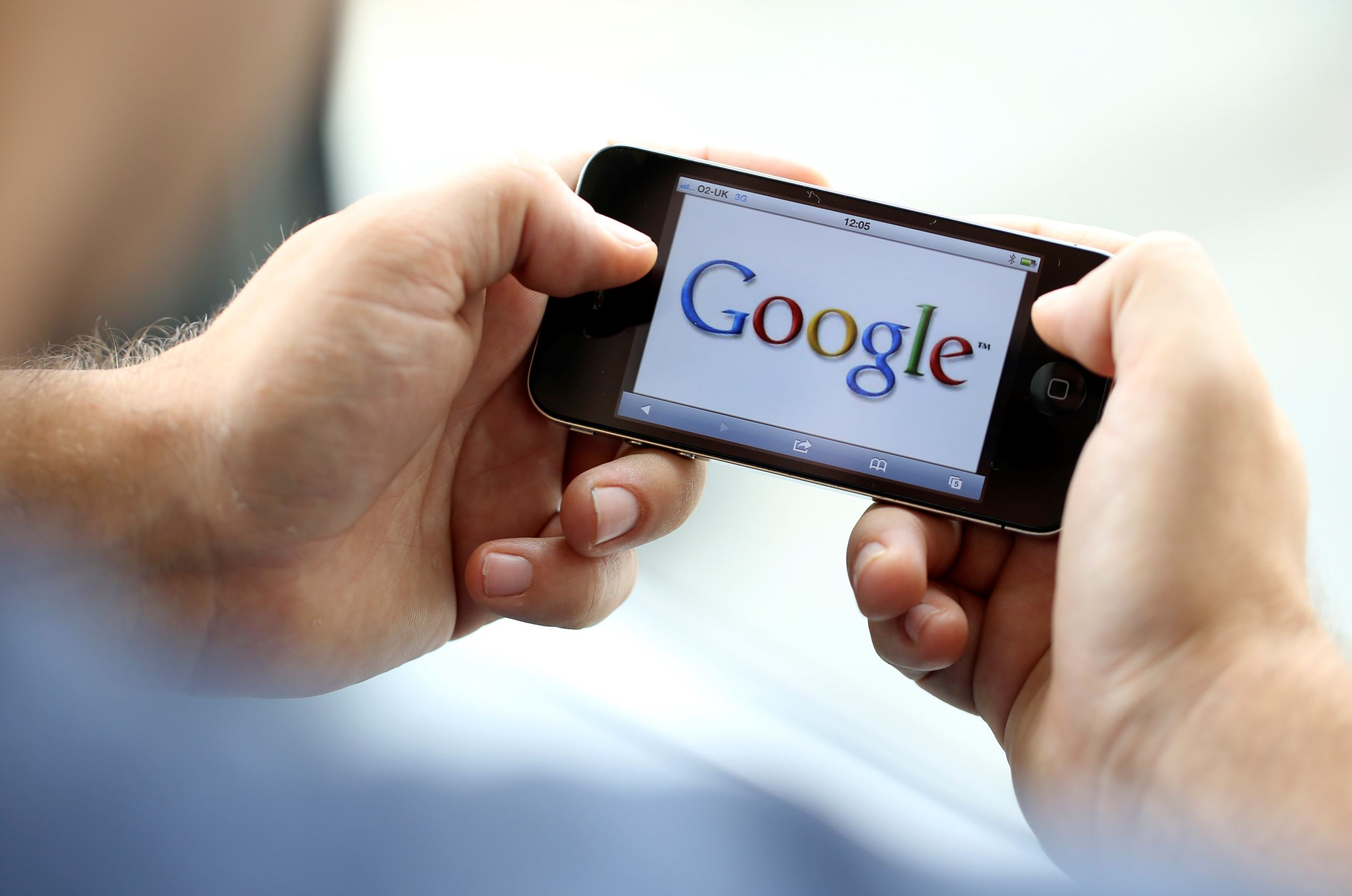 The Google Inc. company logo is seen on an Apple Inc. iPhone 4 smartphone in London, U.K., on Wednesday, Aug. 29, 2012.
