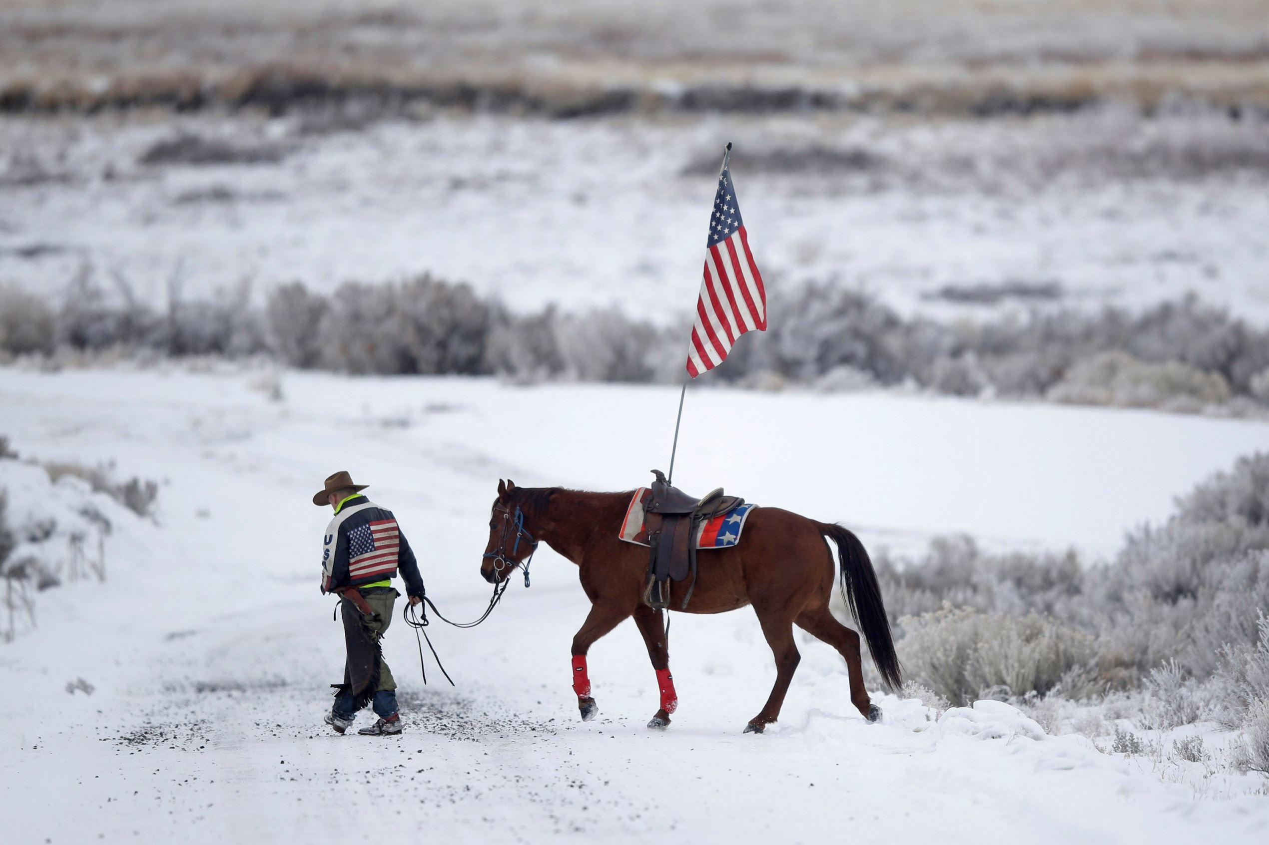 In this Jan. 7, 2016, file photo, cowboy Dwane Ehmer, of Irrigon, Ore., a supporter of the group occupying the Malheur National Wildlife Refuge, walks his horse near Burns, Ore.