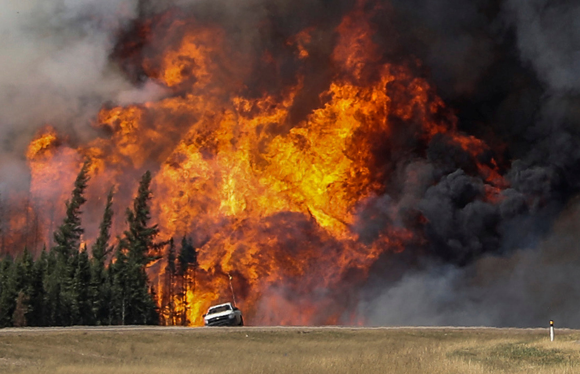 Smoke and flames from the wildfires erupt behind a car on the highway near Fort McMurray, Alta., May 7, 2016.