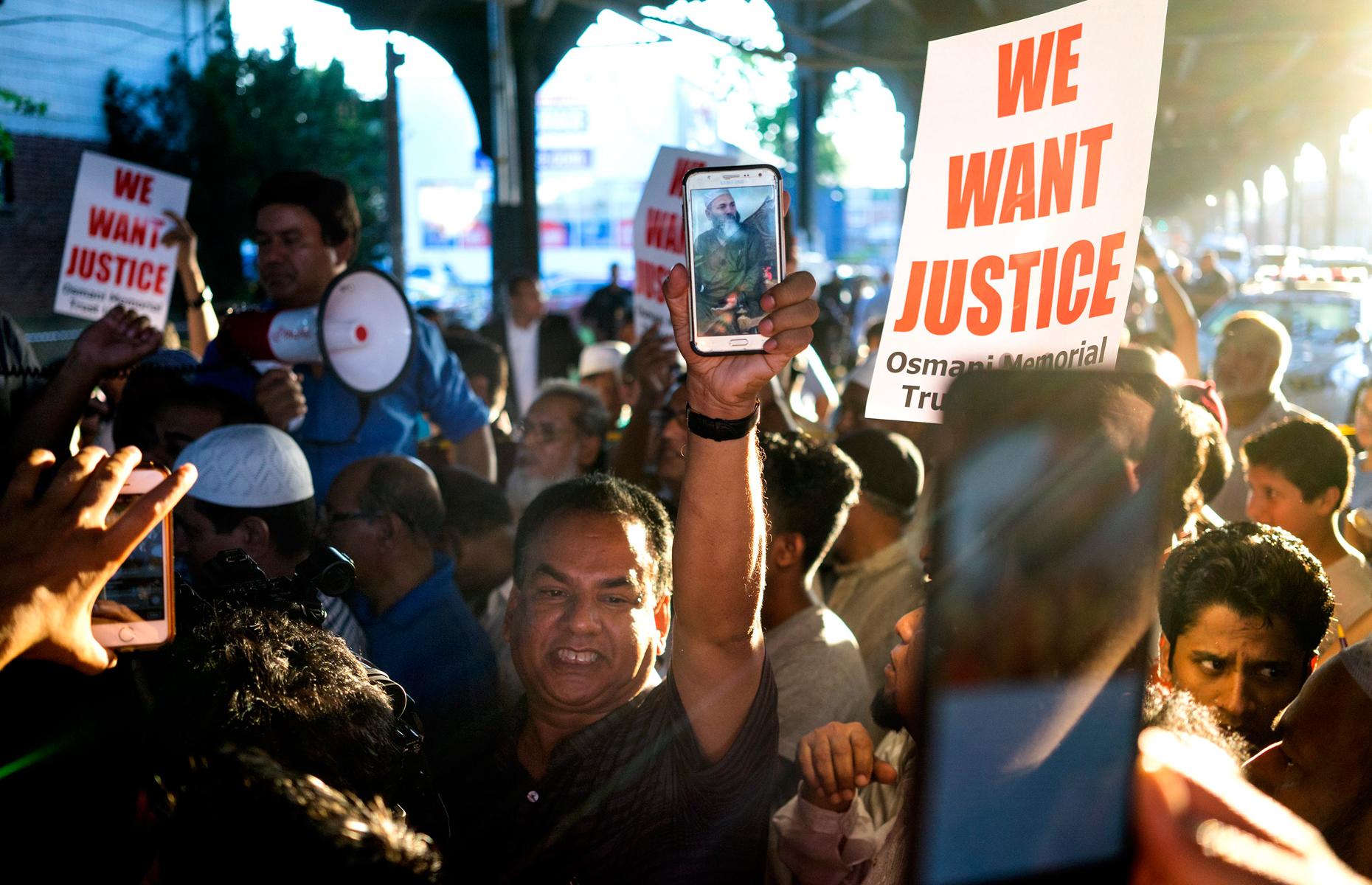 Des gens sont réunis près de la scène du crime à New York le 13 août 2016 après le meurtre de l'imam Maulama Akonhee.