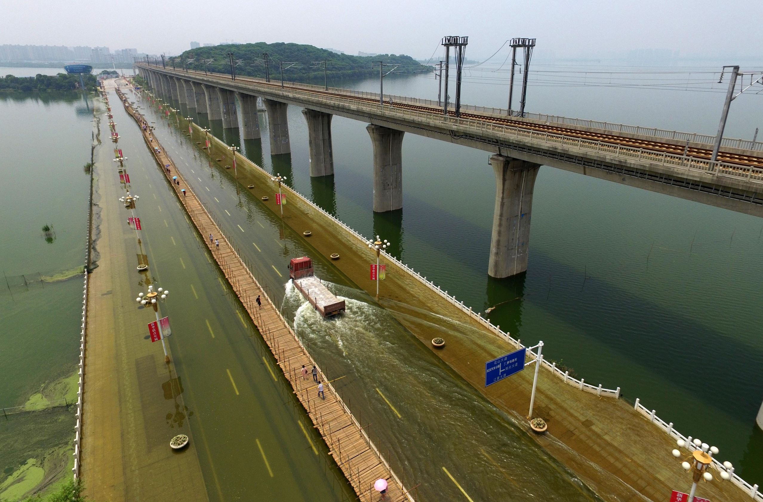 Слайд 64 из 86: Flooding in China - 12 Jul 2016 A temporary boardwalk built on a waterlogged bridge in Wuhan, central China's Hubei Province. A boardwalk was built on a 1400-meter-long bridge submerged by rising water at the Tangxun Lake in Wuhan.