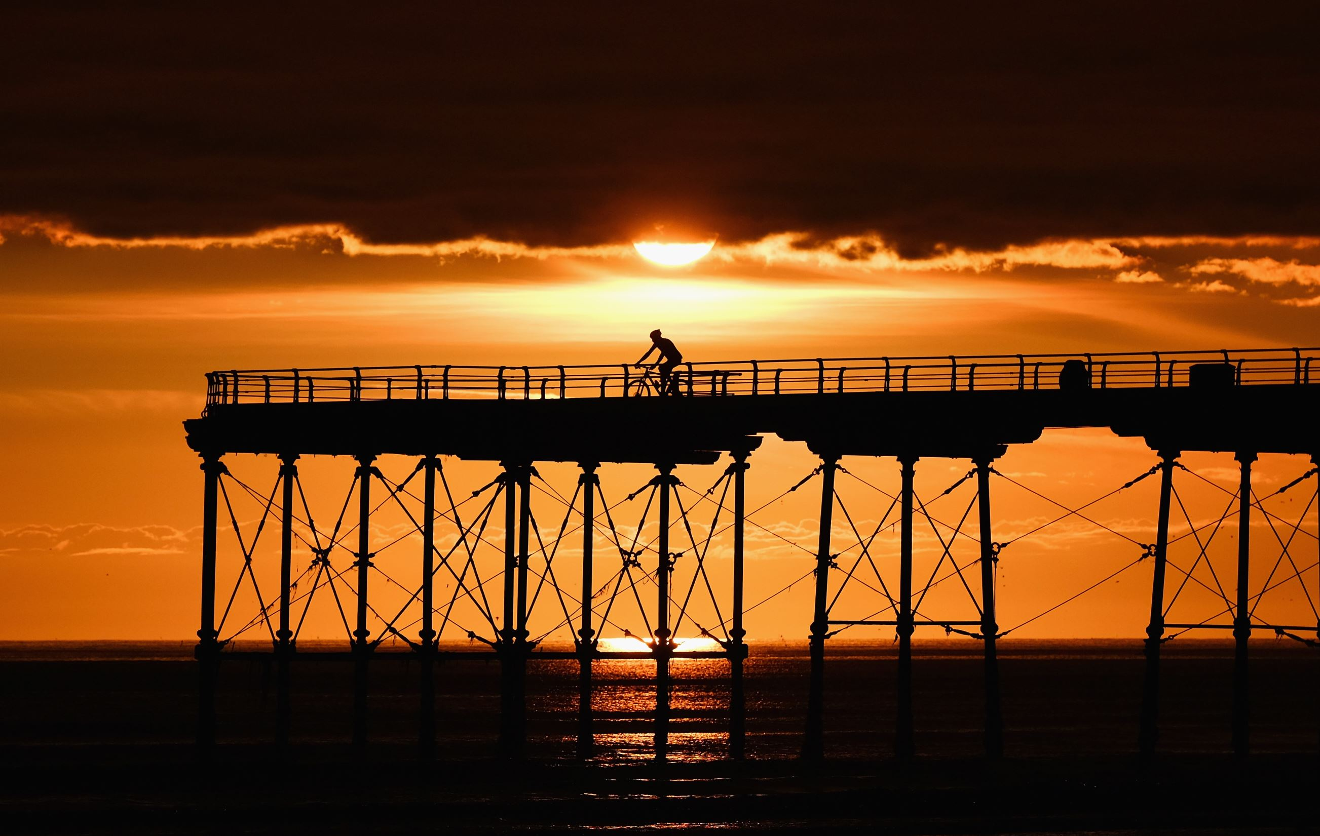 Слайд 72 из 86: SALTBURN-BY-THE-SEA, ENGLAND - AUGUST 15: A cyclist rides to the end of the pier as the sun rises behind clouds on August 15, 2016 in Saltburn-by-the-Sea, England. This week the UK is expected to see some of the hottest days in August for three years wit