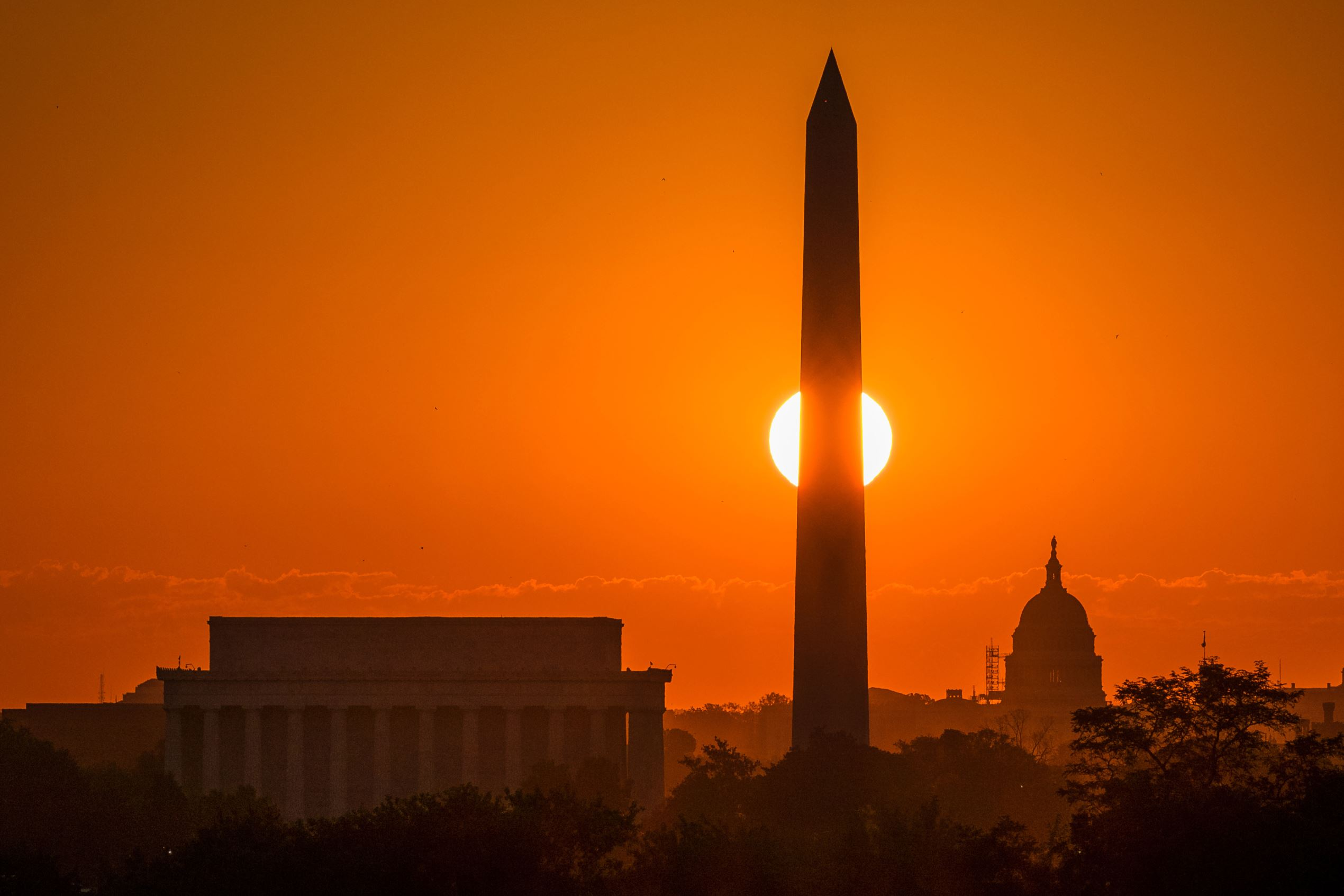Слайд 82 из 86: The rising sun passes behind on the Washington Monument early in the morning Wednesday, Sept. 14, 2016, in Washington on what is expected to be another 90 degree day in the Nation's Capitol. (AP Photo/J. David Ake)