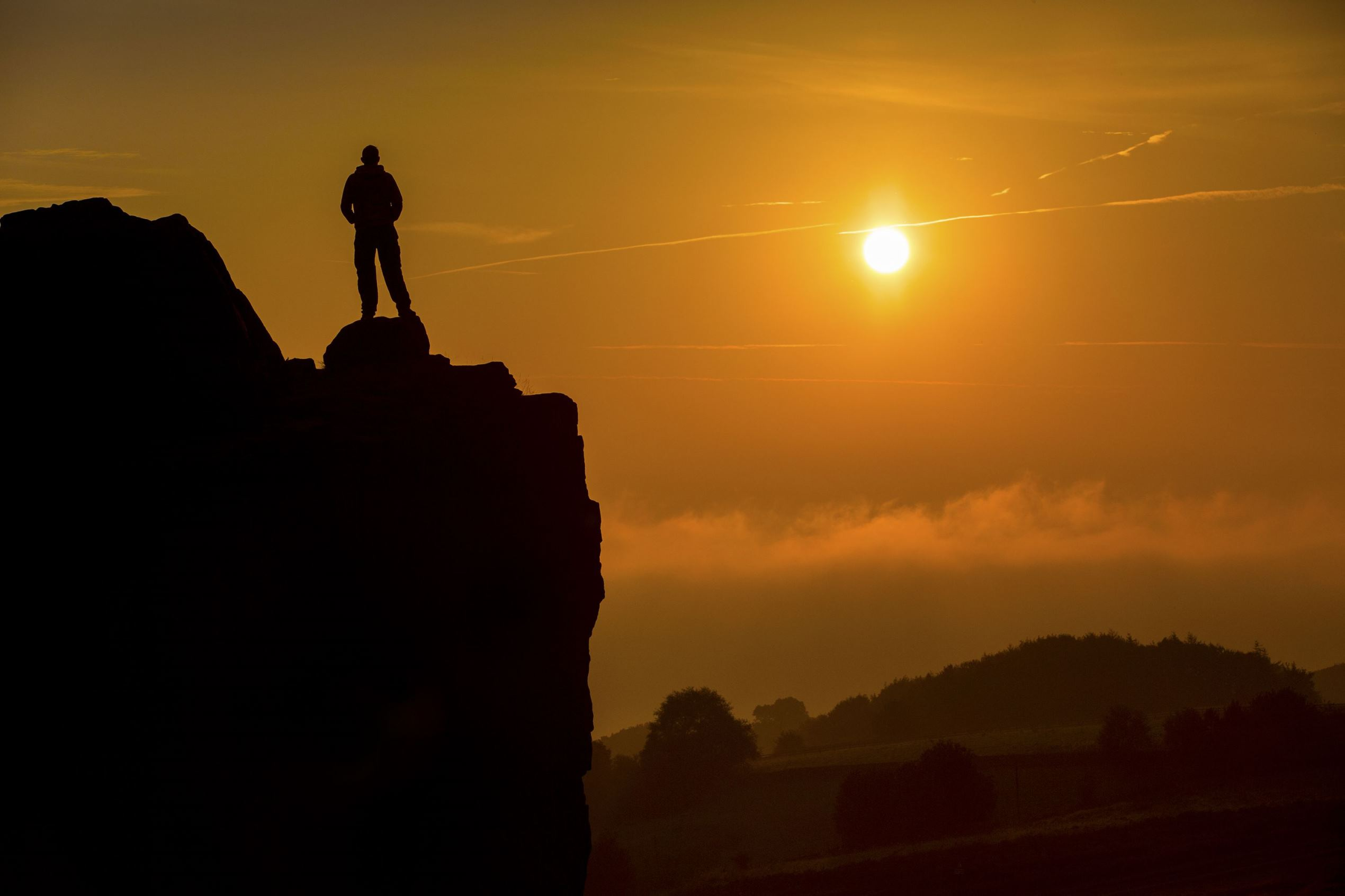Слайд 8 из 86: Seasonal weather, UK - 13 Sep 2016 A man stands on top of the Cow & Calf rocks at Ilkley Moor 1,319ft above the fog covered town of Ilkley to watch this morning's sunrise on what is predicted to be the hottest day in September.