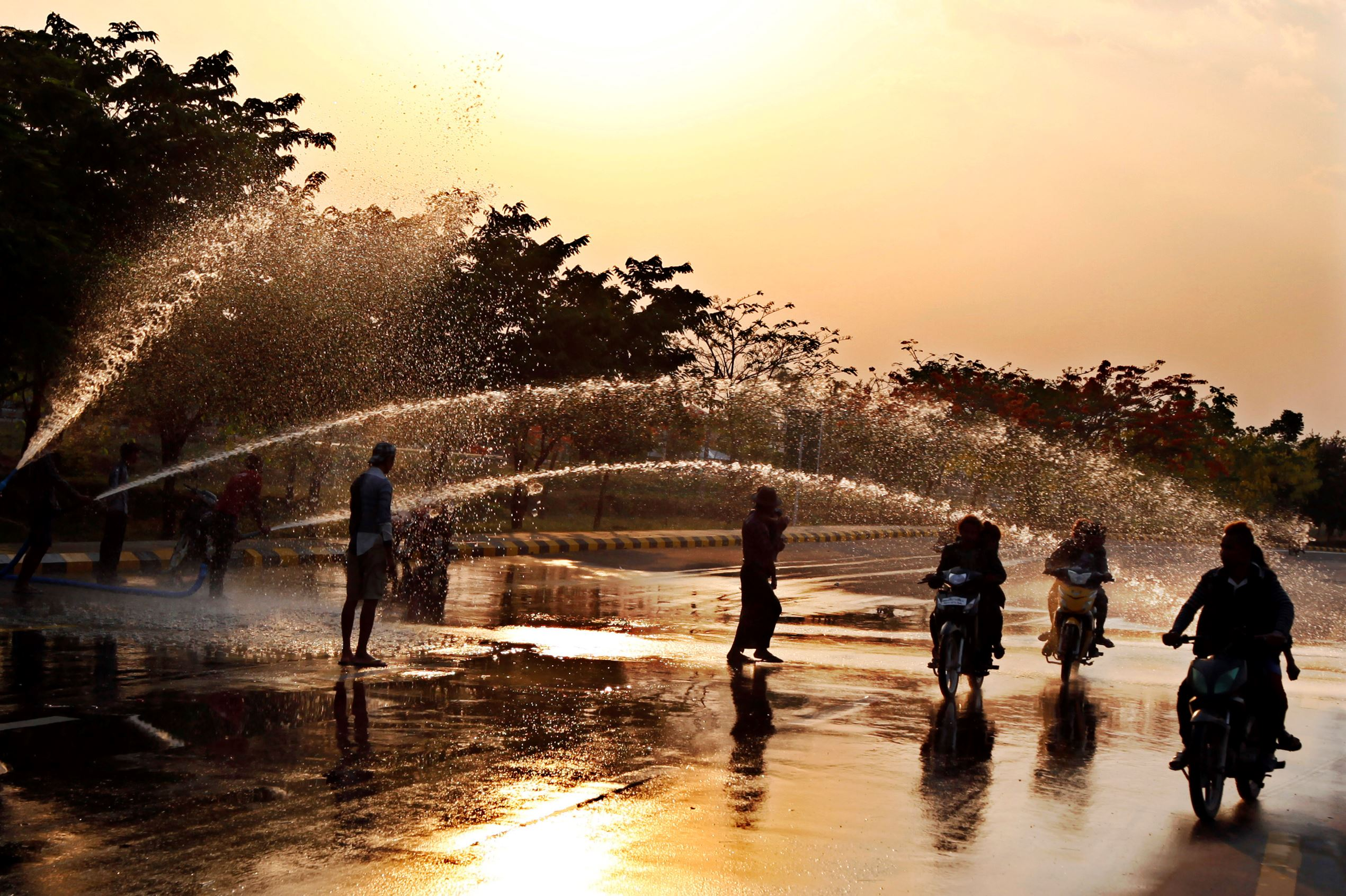 Слайд 37 из 86: Revelers on motorbikes are sprayed with water from the roadside as they participate in the last day of annual new year water festival Saturday, April 16, 2016, in Naypyitaw, Myanmar. The holiday comes at the hottest time of the year and is best known for