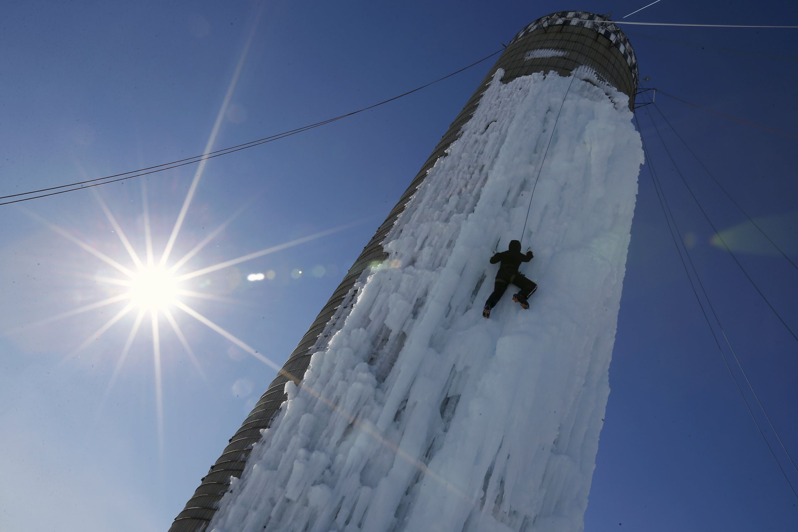 Слайд 9 из 86: An climber ascends a silo covered in ice in Cedar Falls, Iowa, United States, January 17, 2016. The owners have connected hoses to the top of the silo and spray it with water in winter months to freeze the exterior for climbing. REUTERS/Jim Young TPX IMAGES OF THE DAY ...