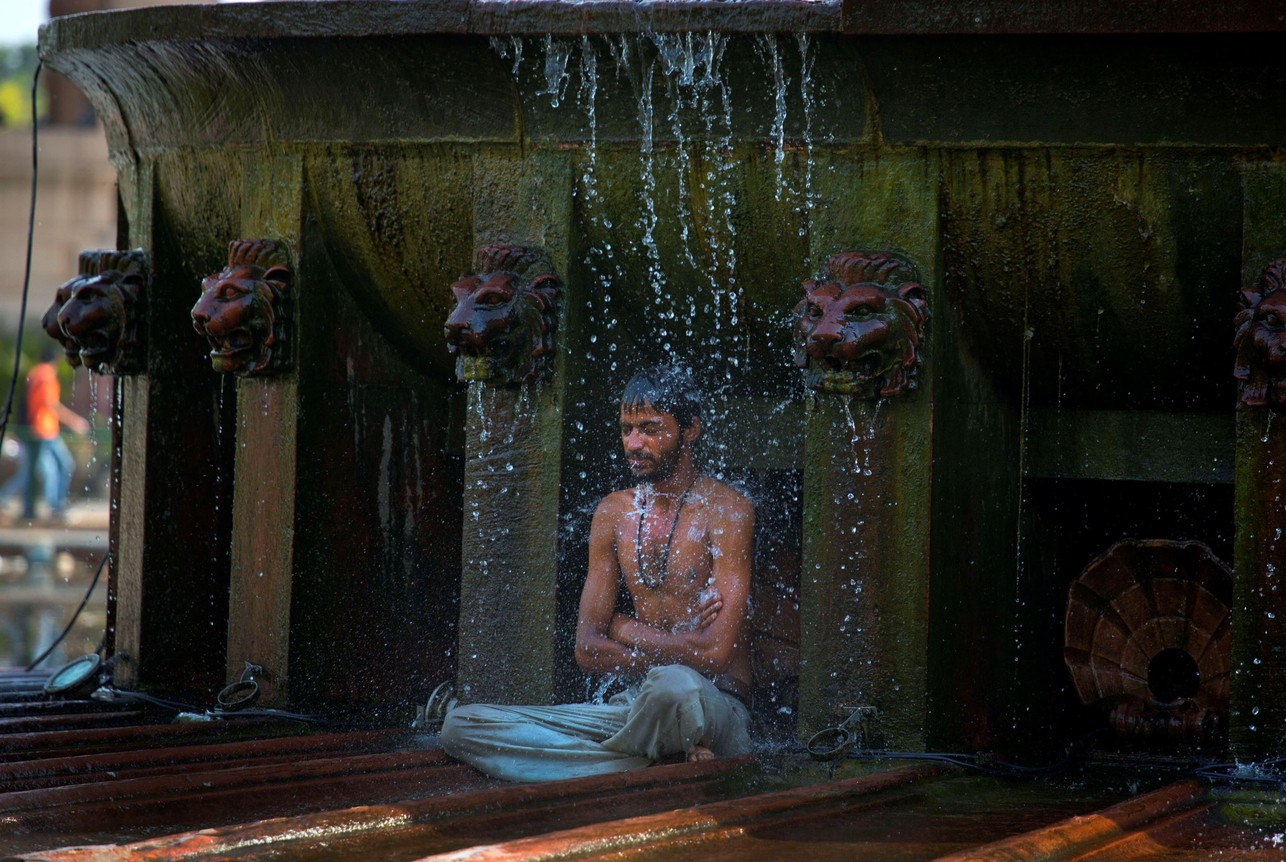 Слайд 43 из 86: An indian man cools himself under a public fountain on a hot afternoon in New Delhi, India, Monday, May 2, 2016. Much of India is reeling under a weekslong heat wave and severe drought conditions that have decimated crops, killed livestock and left at le