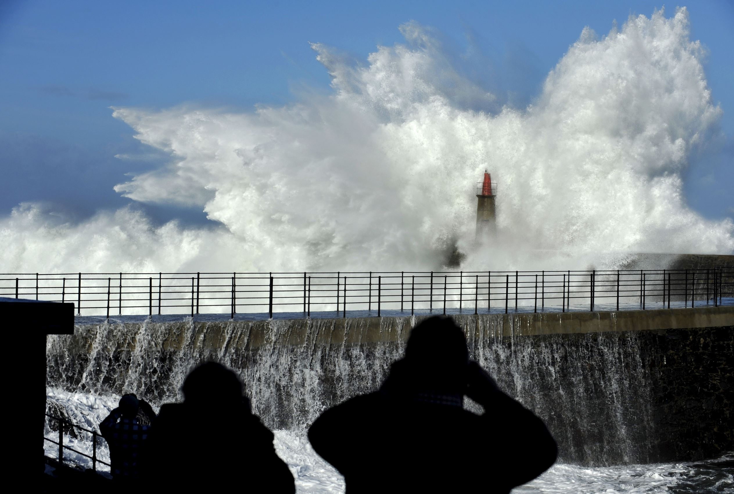 Слайд 2 из 86: People take pictures of huge waves crash on the Viavelez seafront in the northern Spanish region of Asturias January 2, 2016. REUTERS/Eloy Alonso TPX IMAGES OF THE DAY
