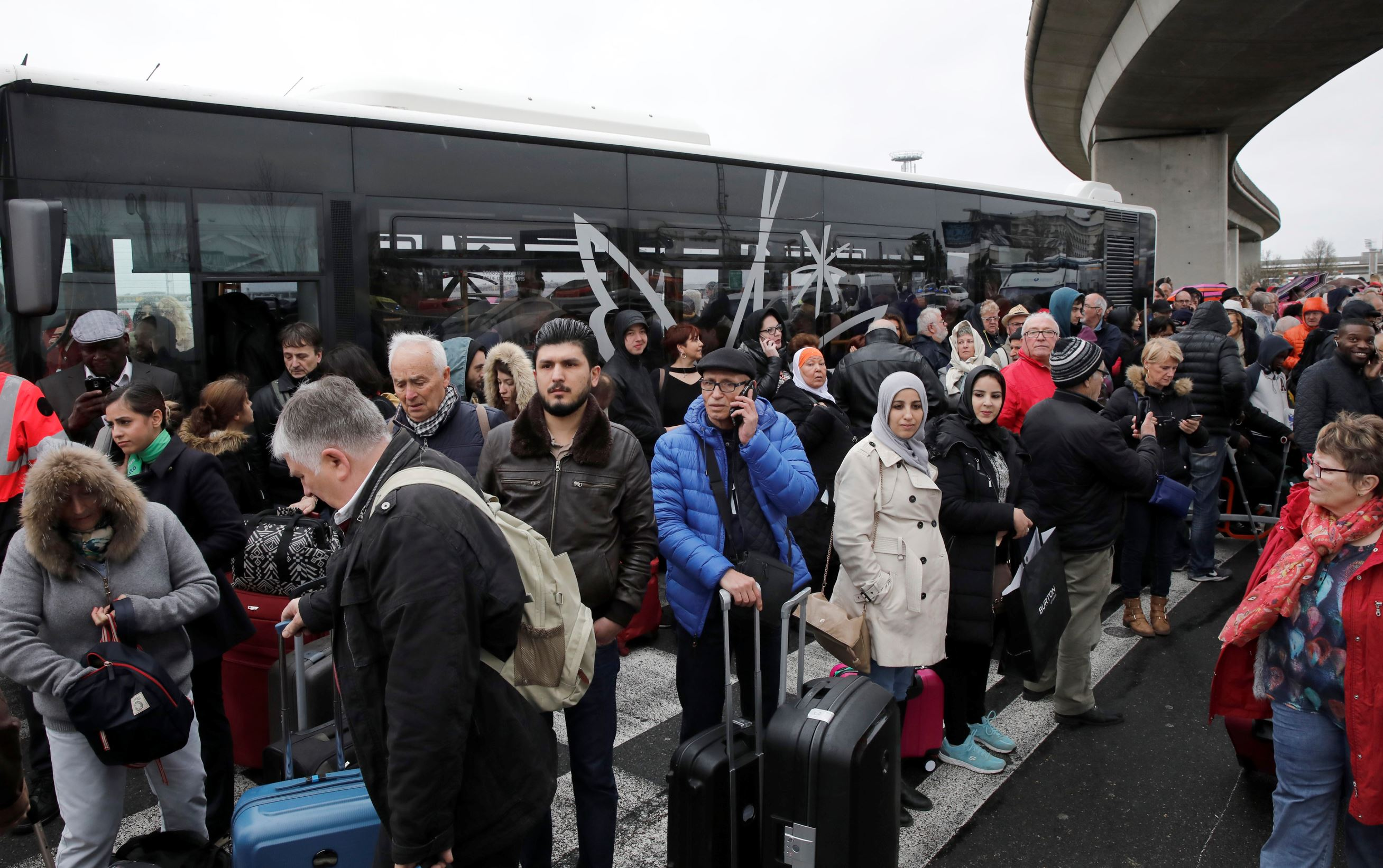 Slide 7 of 14: Passengers wait at Orly airport southern terminal after a shooting incident near Paris, France March 18, 2017.