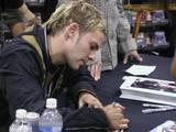 Dom signs an autograph.
