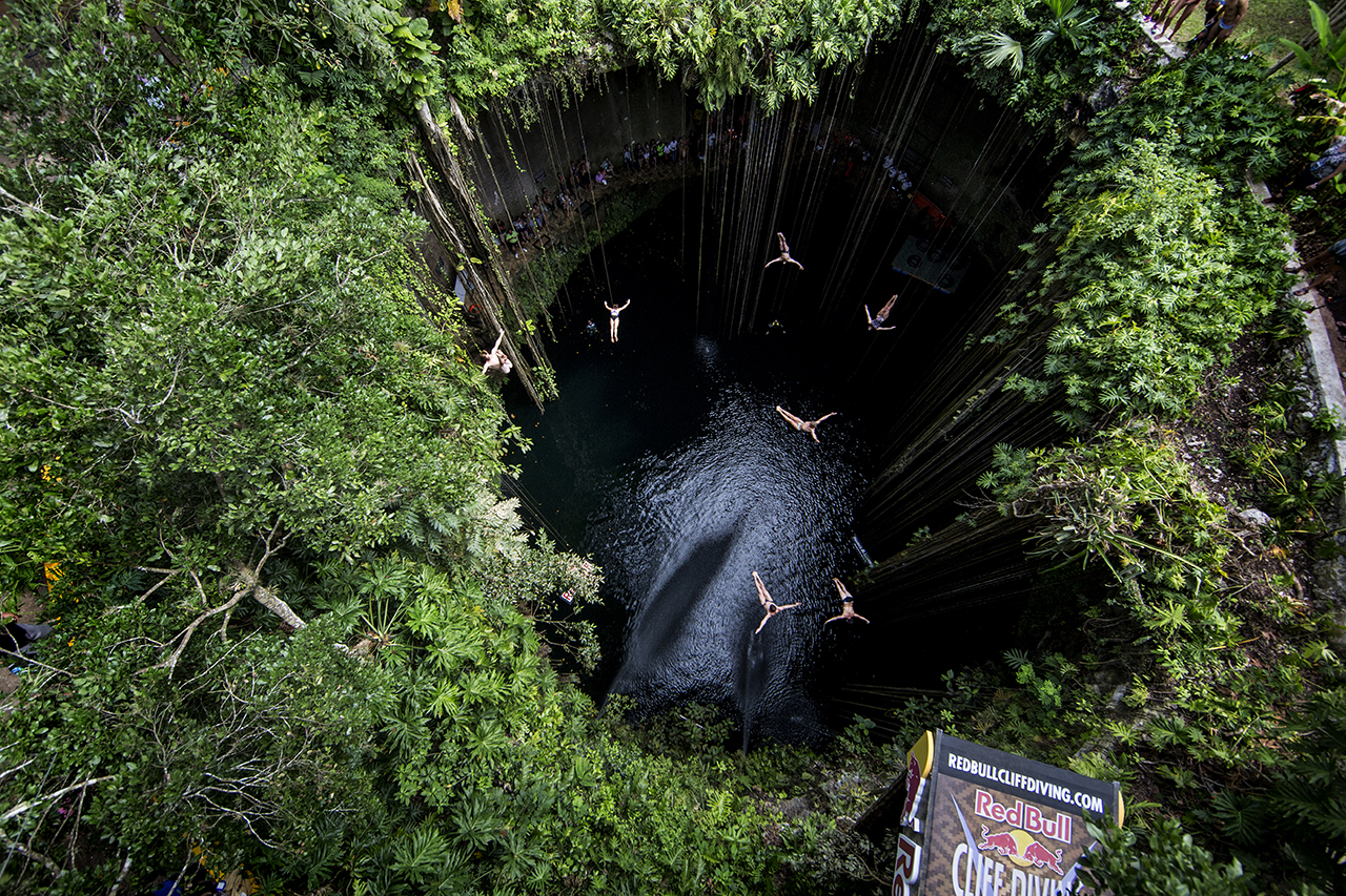 Seven divers perform a mass dive from 19 metres after the second training session of the seventh and final stop of the Red Bull Cliff Diving World Series, Ik Kil cenote, Yucatan, Mexico, on October 16th 2014. // Dean Treml/Red Bull Cliff Diving // P-20141016-00334 // Usage for editorial use only // Please go to www.redbullcontentpool.com for further information. //