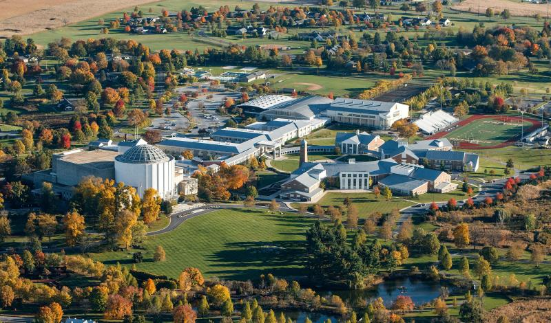 An aerial view of a campus of white and brick buildings spread out over rolling fields and surrounded by trees.