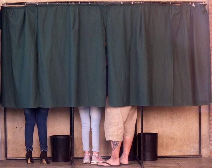 Des électeurs se tiennent dans un isoloir à Villefranche-de-Lauragais, près de Toulouse, le 23 avril 2017 lors du premier tour de l'élection présidentielle française / AFP