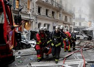 Firefighters evacuate an injured person during an explosion in the 9th arron ...