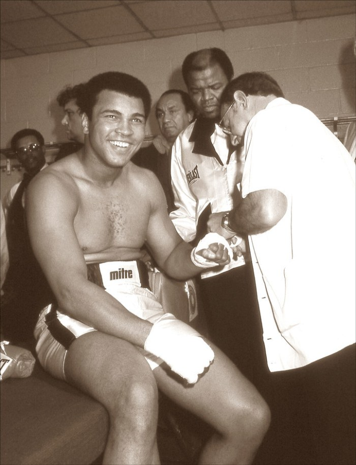 Minutes before the fight, Angelo Dundee tapes Ali's hands in the locker room.