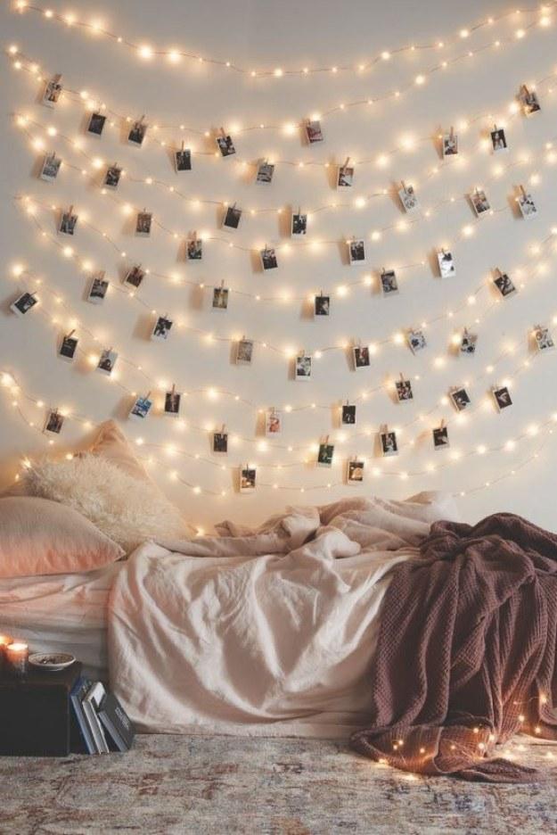 Cuelga lucecitas de navidad y fotos Polaroid contra una pared blanca.