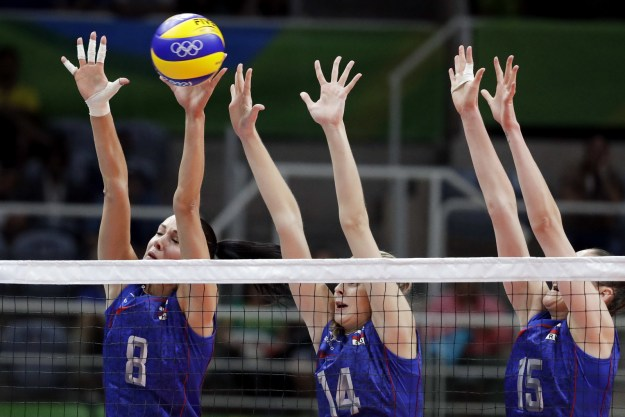 Russia's volleyball team jumps to block a shot by Argentina.