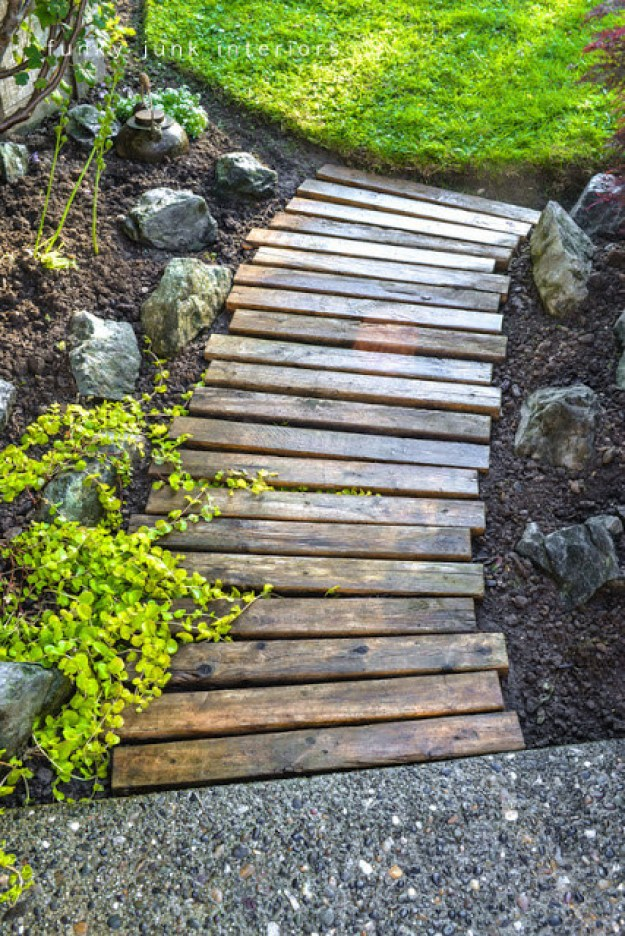 Stain a bunch of the boards, and dig out a little earth, then set them up as a pathway.