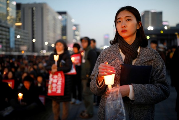 Meanwhile, anti-Park protesters held a candlelit vigil down the road from the court Friday evening to show their support for the decision.