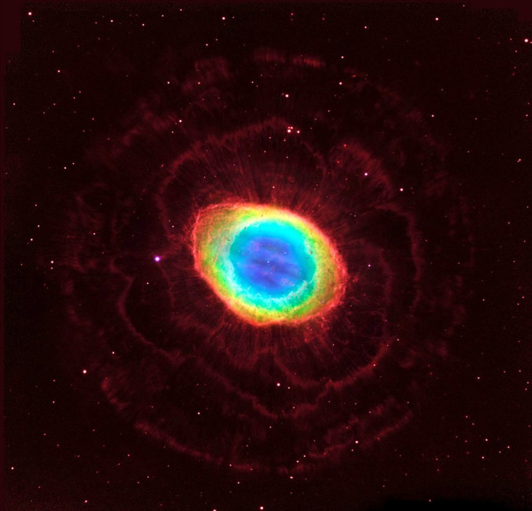 In this composite image, visible-light observations by NASA's Hubble Space Telescope are combined with infrared data from the ground-based Large Binocular Telescope in Arizona to assemble a dramatic view of the Ring Nebula, a glowing gas shroud around an old, dying, sunlike star. The nebula's distinctive shape makes it a popular illustration for astronomy books.