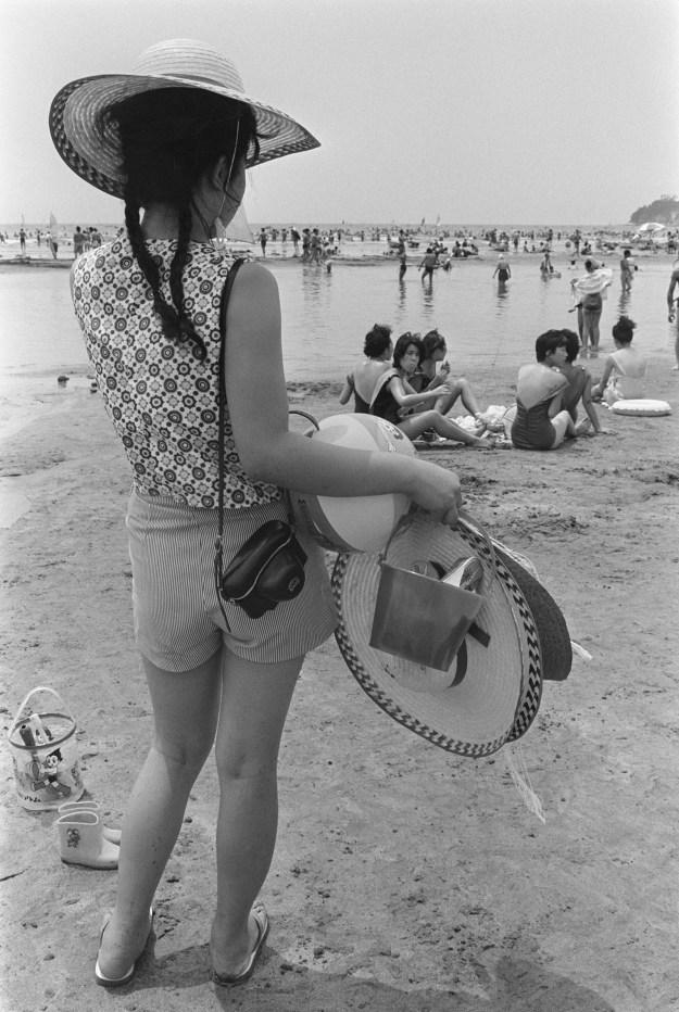 同じく1964年の材木座。カメラを持って、佇む女性。