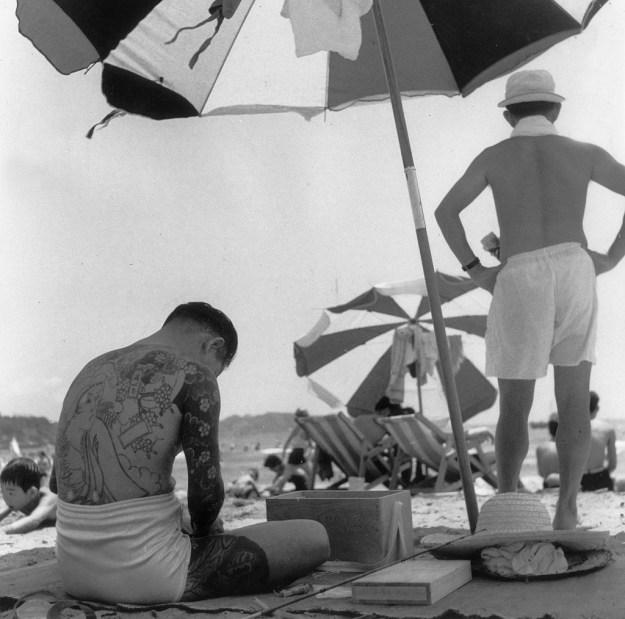 1955年、刺青の入った男性とパラソル。