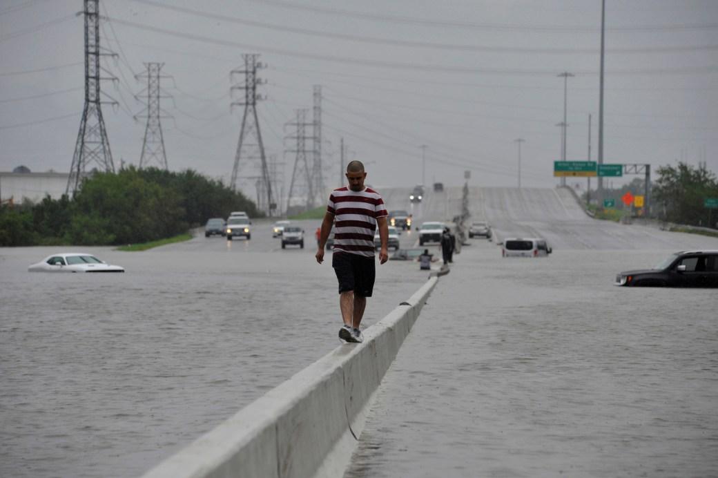 Un motociclista varado escapa del agua en la Interestatal 225 en Houston luego de que el huracán Harvey inundara masivamente con lluvias la costa del Golfo de Texas, 27 de agosto de 2017.