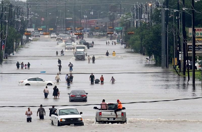 Personas caminando en medio del agua en Telephone Road en Houston, el 27 de agosto de 2017.