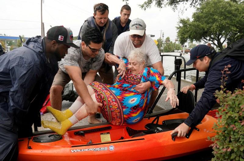 Sterling Broughton es pasado de un bote de rescate a un kayak luego de que las aguas del huracán Harvey se elevaran en Dickenson, Texas, 27 de agosto de 2017.