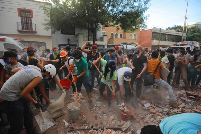 Rescuers and residents look for victims amid the ruins of a building that had been knocked down by the quake.