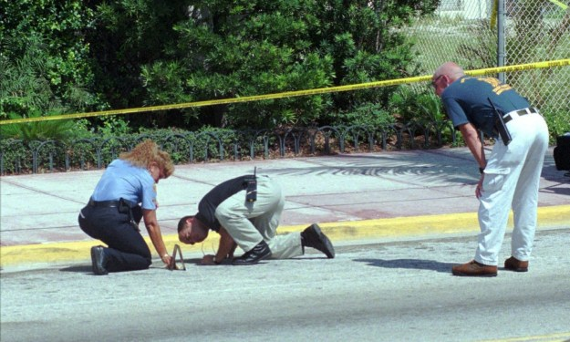 Others combed the ground for clues surrounding Versace's home.