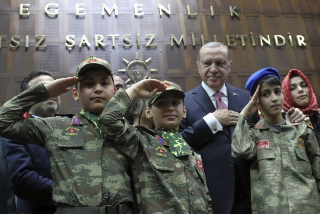 And here he is with children in commando uniforms outside the floor of Turkey's parliament last Tuesady.