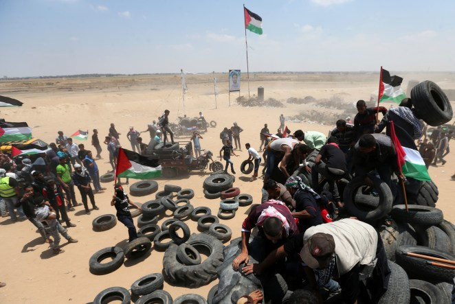 Palestinians collect tires to be burned during a protest marking the 70th anniversary of Nakba, at the Israel-Gaza border on May 15.