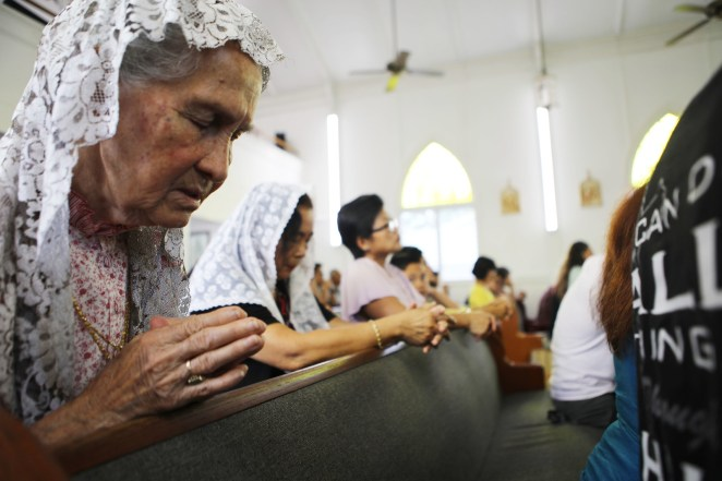People pray during Sunday Mass at Sacred Heart Church on May 6. One parishioner's home was destroyed by lava flows.