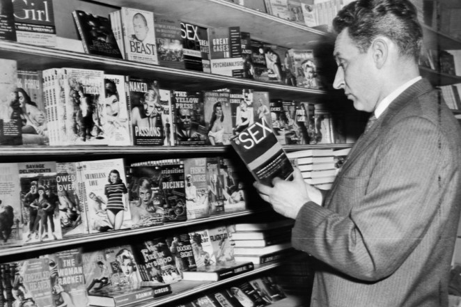 An NYPD detective examines erotic books during a raid on illegal pornographic materials in 1960.