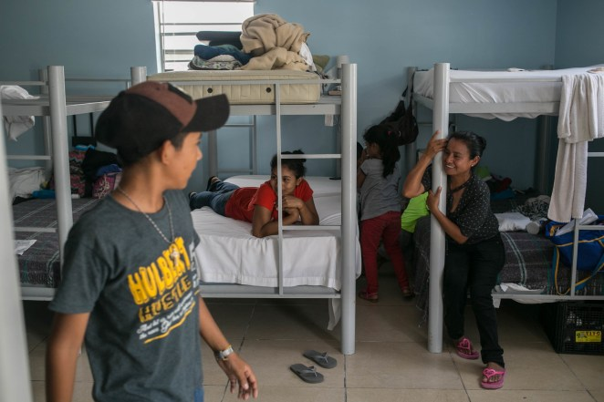Patricia (center) and Maria (right) sit in their beds at the Senda De Vida shelter in Reynosa and watch as children play with one another.