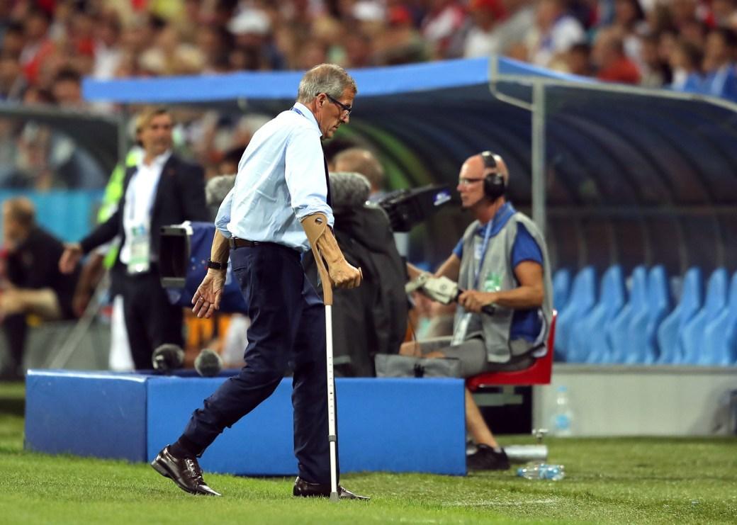O técnico uruguaio Óscar Tabárez, portador de uma doença degenerativa que dificulta os movimentos, caminha de volta para o banco com o auxílio de uma muleta.