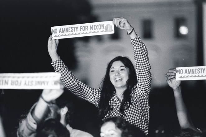 "A demonstrator holds a ""No Amnesty For Nixon"" sign outside the White House."