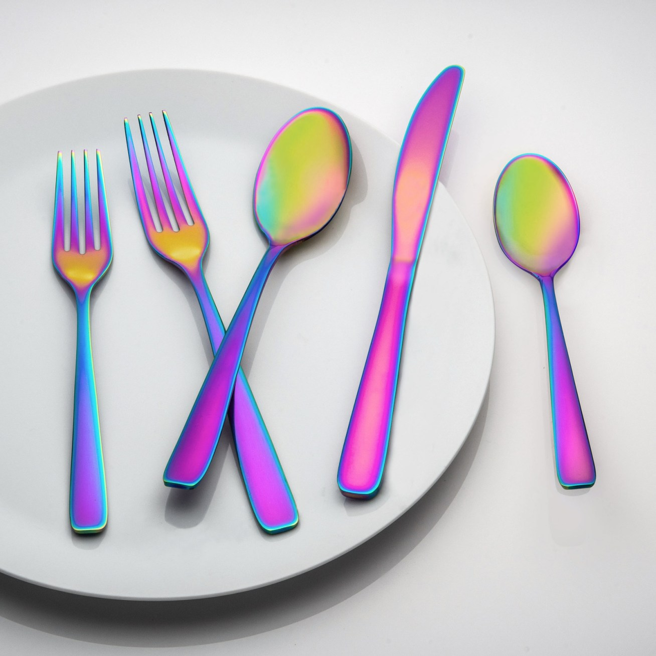 """Promising review: """"What a fun set! The iridescent colors will make any boring dinner table pop with personality. The set is well-made, has a nice sturdy weight, and is such a good deal for a 20-piece set."""" —SFShopper AudPrice: .94"""