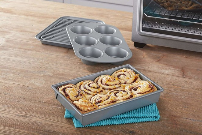 The four-piece set includes a baking pan, cooling rack, cake pan, and muffin pan. The pieces are dishwasher-safe, but hand-washing them is recommended. 