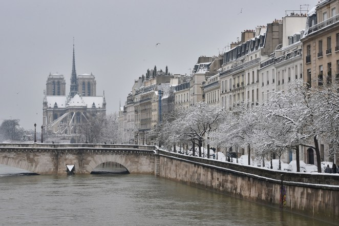 Snow blankets the bank of the River Seine and Notre-Dame Cathedral.
