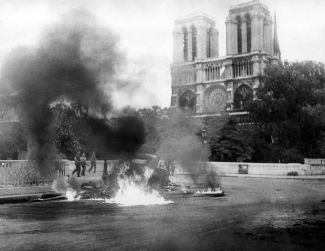 "A photo taken circa Aug. 23, 1944 during World War II shows a flaming vehicle close to the Pont Saint-Michel and Notre Dame Cathedral Notre-Dame as part of the ""Battle of Paris"" opposing the French Forces of the Interior and remaining Nazi forces, a few days before the Liberation of Paris on Aug. 25, 1944."