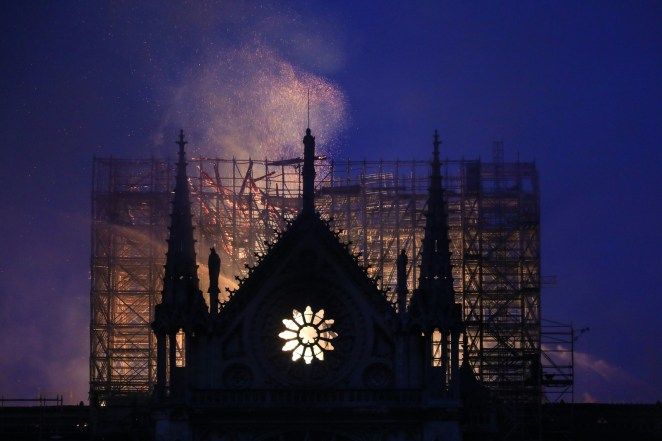 Smoke and flames rise during a fire at the landmark Notre-Dame Cathedral on the evening of April 15, 2019.