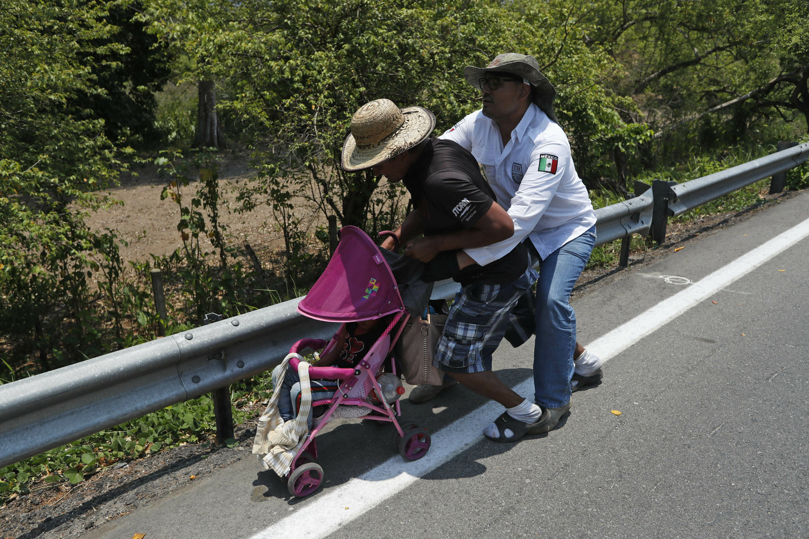 A Central American migrant pushing a child in a baby carriage is detained by a Mexican immigration agent from behind.