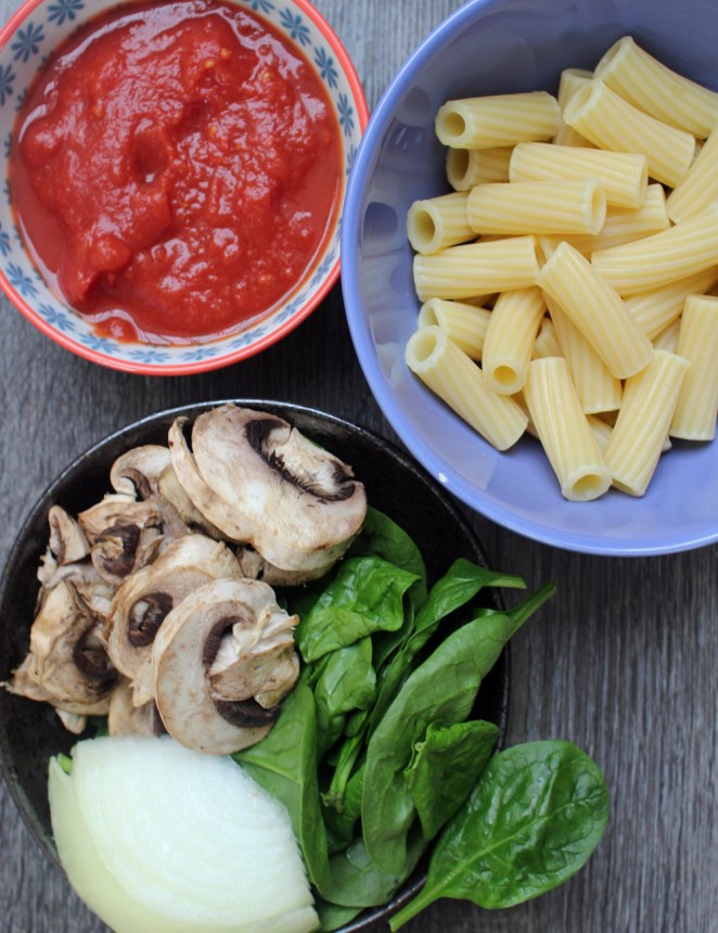 ⅙ large onion, dicedWhite button mushrooms, slicedOlive oil, to tasteHandful of fresh spinach, roughly torn½ cup canned crushed tomatoesKosher salt, to tasteFreshly ground black pepper, to tasteRed pepper flakes, to taste1 cup rigatoni or pasta of choice, cooked according to package instructions