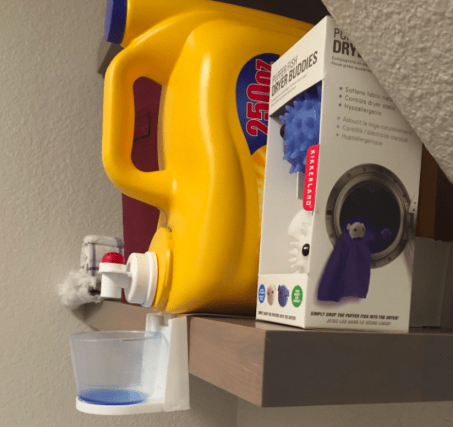 "Promising review: ""Very happy with this product. Fits nicely underneath to hold the cup without dangling too low and the fact that I can just Command Strip attach it to the bottom of the detergent means that it can't/won't slip off the head of the dispenser, as many similar alternatives have been reviewed to do."" —Amazon CustomerGet it from Amazon for $2.99."