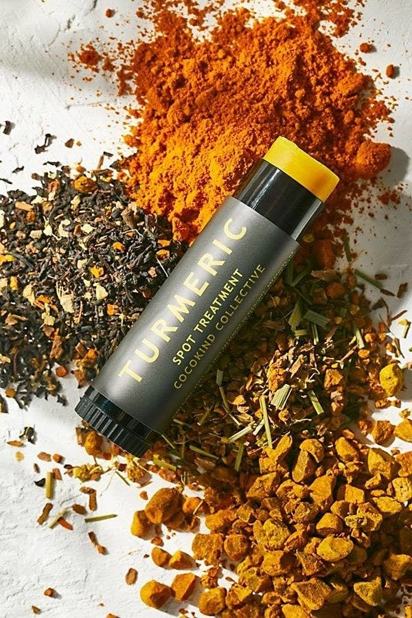 The spot treatment in a tube that looks like a Chapstick tube on top of a pile of tumeric and other ingredients