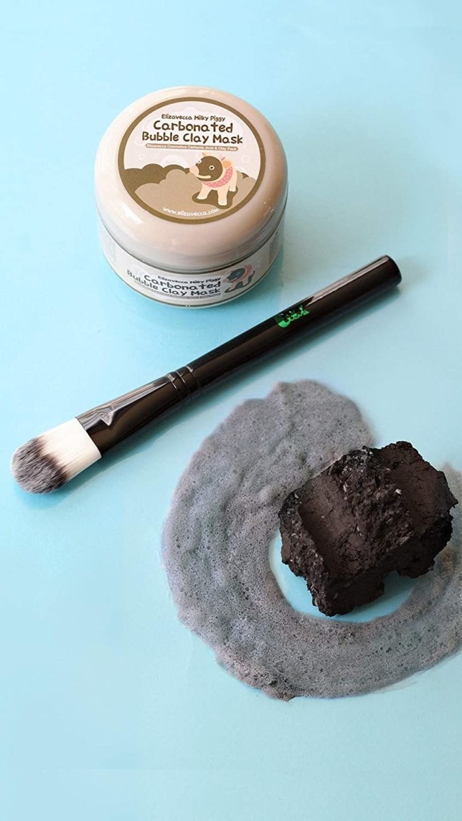 Elizavecca Milky Piggy clay mask next to a brush applicator and piece of charcoal